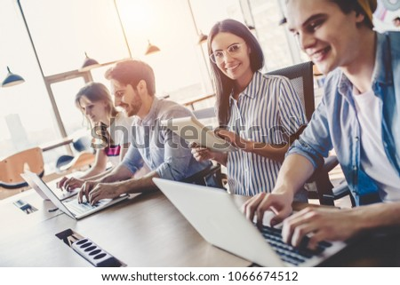 Group of young business people are working together in modern office with laptop, tablet, smart phone, notebook. Successful team in coworking. Freelancers. #1066674512
