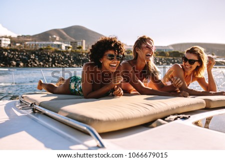 Beautiful young women relaxing on a private yacht deck in the sea. Three female friends sunbathing on luxury yacht and having a great time. #1066679015