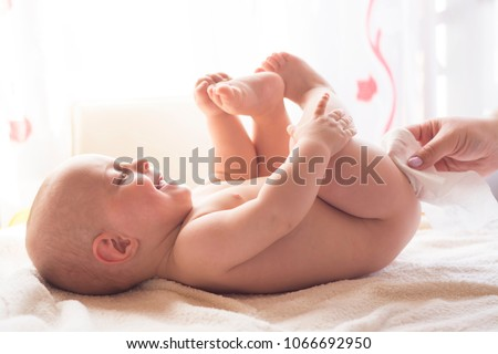 Hygiene - young mom wiping the baby skin with wet wipes carefully. Cleaning wipe, pure, clean #1066692950