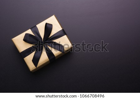 Hands holding wrapped gift box with colored ribbon as a present for Christmas, new year, mother's day, anniversary, birthday, party,  on black background, top view. Present for a colleague at work. #1066708496