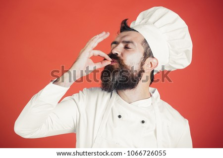 Professional chef man showing sign for delicious. Male chef in white uniform with perfect sign. Serious satisfied bearded chef, cook or baker gesturing excellent. Cook with taste approval gesture. Royalty-Free Stock Photo #1066726055