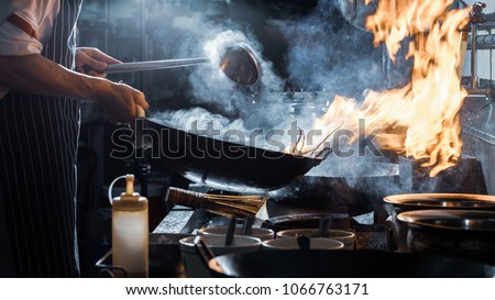 Chef is stirring vegetables in wok, vintage filter Royalty-Free Stock Photo #1066763171