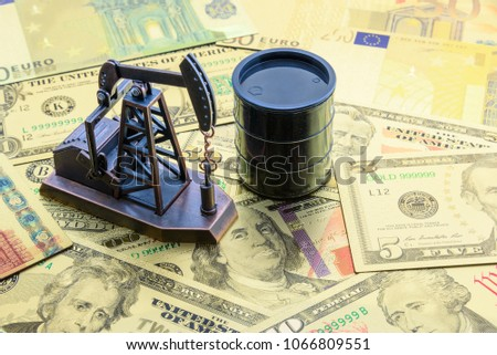 Petroleum, petrodollar and crude oil concept : Pump jack and a black barrel on US USD dollar notes, depicts the money received or earned from sales after investment in the development of oil industry. #1066809551