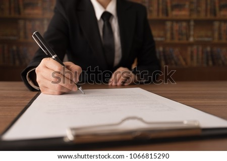 legislation law concept. lawyer signing legal document and agreement on desk in law office. #1066815290