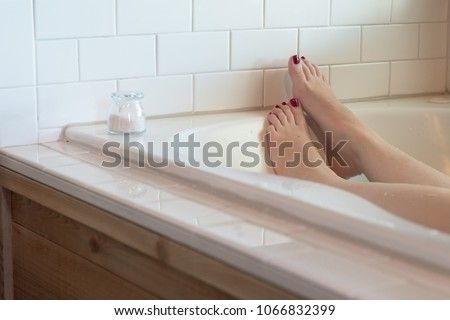 Women's feet with dark purple nail polish in a luxurious bathtub surrounded by white subway tile, with wood along the side. a small glass container of pink bath salts rests at the edge. #1066832399