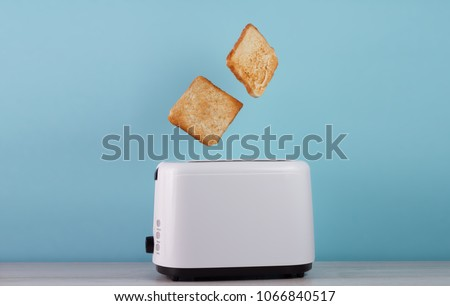 Roasted toast bread popping up of stainless steel toaster on a blue backgroun.Space for text #1066840517