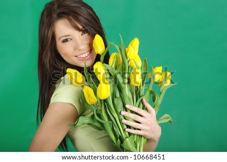 Smiling girl with yellow tulips. green background #10668451