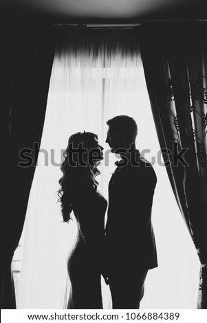 portrait of a romantic couple , silhouette, couple of lovers groom and bride at the window, black and white photography .