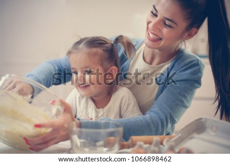 Mother and daughter baking cookie and mixing dough. #1066898462