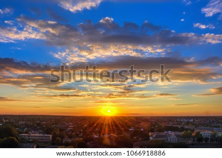 Sun, sky with clouds over city at sunset. #1066918886