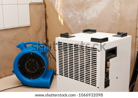 Elimination of water damage with dryer and fan #1066932098