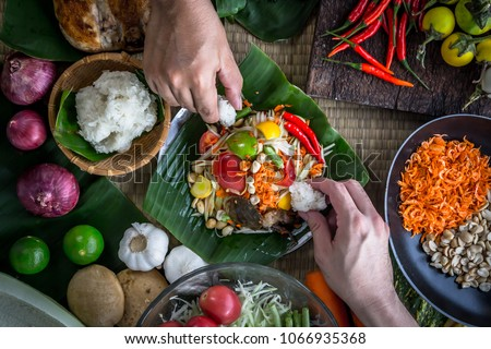 """Hands holding sticky rice to eat with Thai papaya salad or what we call """" Somtum """" in Thai with ingredients. The famous local Thai street food with hot and spicy dish. Food stylish photography concept #1066935368"""