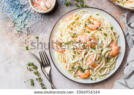Italian pasta fettuccine in a creamy sauce with shrimp on a plate, top view #1066956164