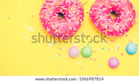 Sprinkled Pink Donut. Frosted sprinkled donut on yellow background. #1066987814