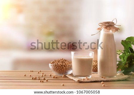 Reptientes with soy milk and grains on a wooden table and rustic kitchen background. Alternative milk concept. Front view. Horizontal composition #1067005058