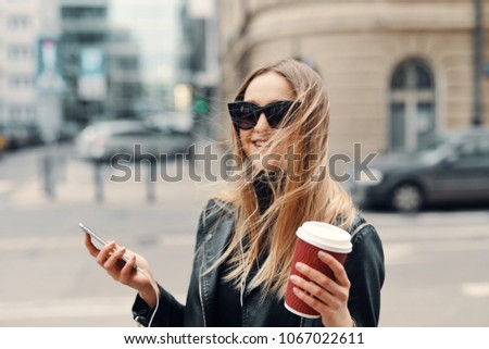 Pretty girl stand on the street listen music from her headphones and drink coffee, windy weather #1067022611