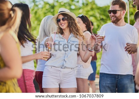 Group of people dancing and having a good time at the outdoor party/music festival #1067037809