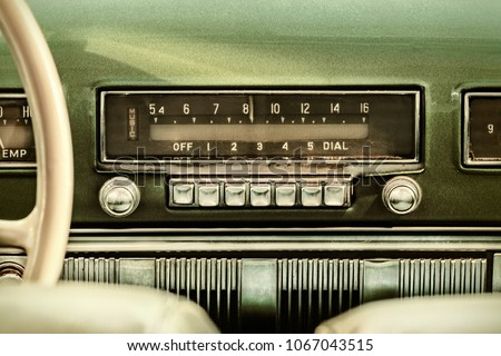 Retro styled image of an old car radio inside a green classic car Royalty-Free Stock Photo #1067043515