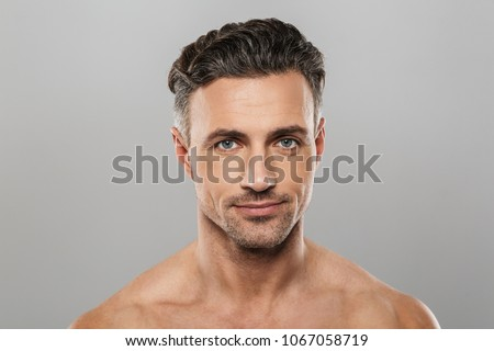 Photo of smiling mature man standing isolated over grey wall background naked. Looking camera. #1067058719