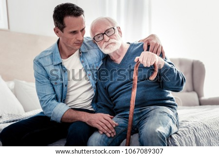 Father and son. Nice peasant thoughtful father and son sitting together and thinking about their life while feeling sad #1067089307