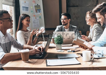 Working together. Group of young modern people in smart casual wear discussing business and smiling while sitting in the creative office #1067101610