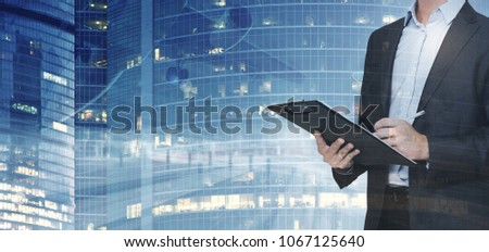 Successful businessman signing document on clipboard on industrial business background #1067125640