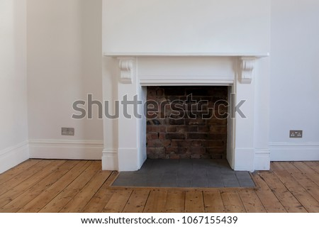 Victoriran wooden fireplace surround with white walls #1067155439