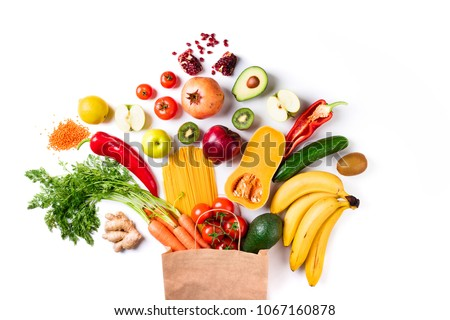 Healthy food background. Healthy food in paper bag pasta, vegetables and fruits on white. Shopping, vegetarian, balanced food concept. Top view