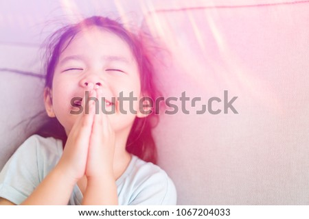 Little girl praying in the morning at home.Little asian girl hand praying for thank GOD,Hands folded in prayer concept for faith,spirituality and religion. #1067204033