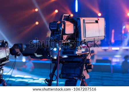 Professional TV camera with a large lens on the tripod during the recording of the concert Royalty-Free Stock Photo #1067207516