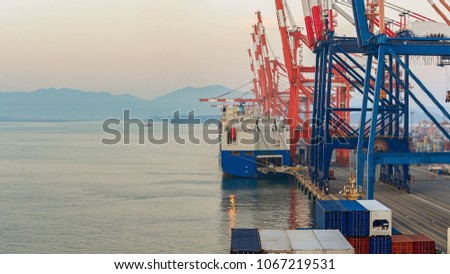 Pure car/truck carrier cargo vessel and container handling gantry cranes (ship-to-shore cranes) on cargo terminal of industrial commercial port. #1067219531