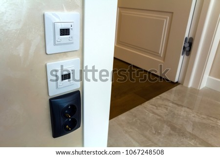 Modern house interior with warm floor controller panels on the wall, wooden parquet and white door #1067248508