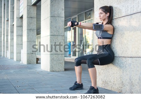 Young sportswoman doing wall sit exercise outdoors. #1067263082