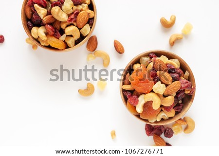 healthy snack: mixed nuts and dried fruits in wooden bowl on white background, almond, pineapple, cranberry, papaya, apple, strawberry, cherry, apricot, cashew. #1067276771