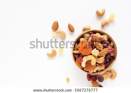 healthy snack: mixed nuts and dried fruits in wooden bowl on white background, almond, pineapple, cranberry, papaya, apple, strawberry, cherry, apricot, cashew. #1067276777