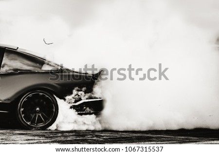 Side view car drifting on track with grain, Sport car wheel drifting and smoking on track.  #1067315537