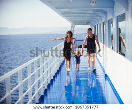 Happy family with cute son on summer vacation. Family travelling on cruise ship on sunny day. Family rest concept. Father, mother and child walk on deck of cruise liner with sea on background. #1067351777