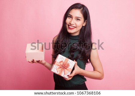 Young Asian woman open a golden gift box on pink background #1067368106
