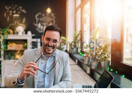Portrait of a successful entrepreneur holding eyeglasses while sitting at the cafe in front of a laptop. Royalty-Free Stock Photo #1067445272