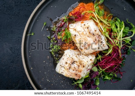 steamed cod fish filet with lettuce as top view on a plate with copy space left #1067495414