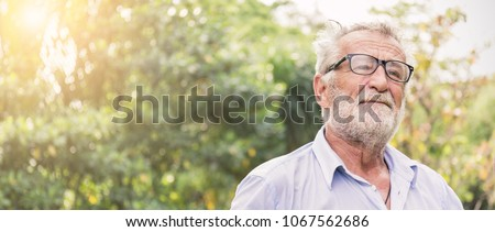 Portrait of stressful sad senior elderly caucasian old man in the park outdoors with copy space. Spring healthcare lifestyle eldery stress painful retirement golden age crisis concept panoramic banner #1067562686