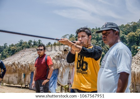 Perak,Malaysia - April 1 2018 : A man is  trying to fire a shot from a traditional blowgun while being assist by local people during a visit at native people village. #1067567951