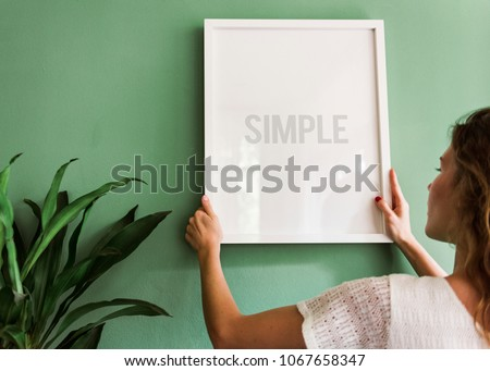 Girl hanging a frame on a green wall