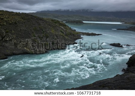 Turbulent waters of the Paine River in Chilean Patagonia. Overcast sky above. Wide shot. Panorama #1067731718