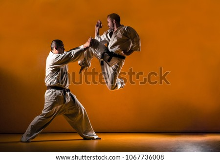 Two karate men fighting in a indoor dojo. Royalty-Free Stock Photo #1067736008