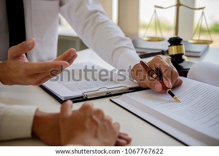 Justice and Law concept. Legal counsel presents to the client a signed contract with gavel and legal law or legal having team meeting at law firm in background #1067767622
