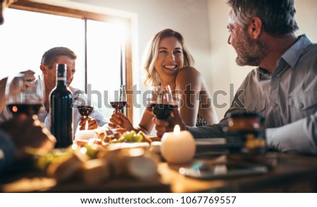 Smiling woman talking with friends sitting at dining tablet at home. Group of people having great time at dinner party. #1067769557