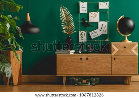 Dark green apartment interior with scandinavian style wooden furniture and designer black and gold decorations #1067812826
