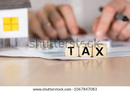 Word TAX composed of wooden letters. Female hand with a pen in the background. Closeup #1067847083