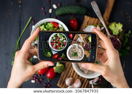 Young woman hands make photo of Israeli hummus with phone. Take social networks smartphone food photography. Raw vegan vegetarian healthy food